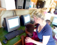 A volunteer prepares a computer for use by a child in the Wild Coast of South Africa